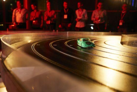 Petites voitures de course sur circuit géant avec joueurs en fond
