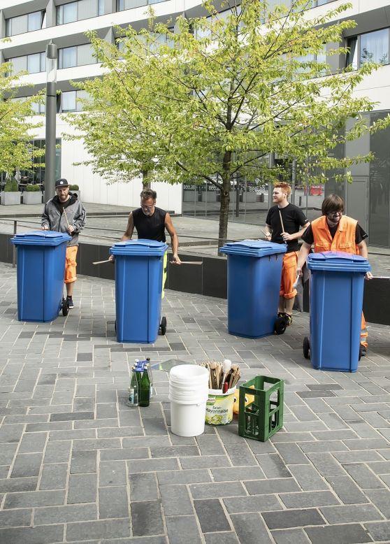 Groupe de musique qui jouent avec des poubelles