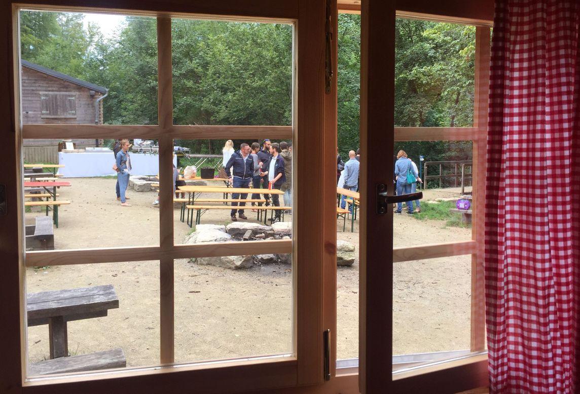 Photo prise de l'intérieur du chalet à travers la fenêtre où les convives discutent autour d'une bière