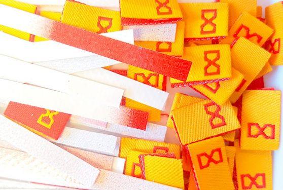 Petites étiquettes jaune et rouge du logotype DONO et bandes de bâche