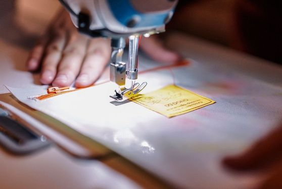 Photographie d'une couturière qui fixe une étiquette DONO sur un sac en bâche
