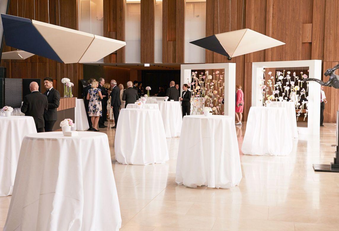 Mise en place des tables à nappes blanches et des décorations florales suspendues dans l'espace dédié à l'événement