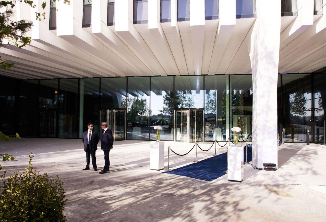 Entrée avec tapis bleu et fleurs devant le nouveau bâtiment Luxempart