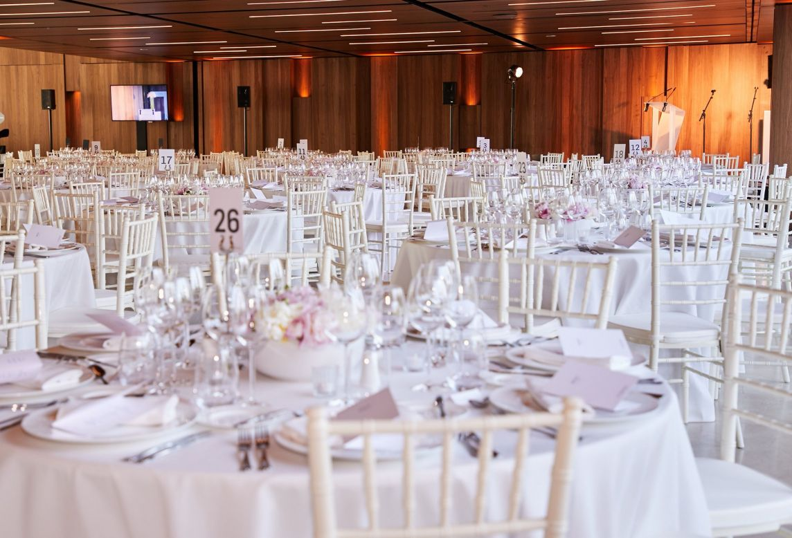 Vue d'ensemble de la salle du dîner de l'événement avec tables nappées blanc et chaises blanches