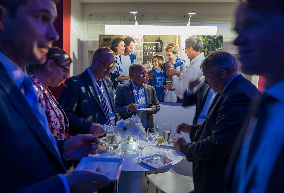 Convives qui mangent autour d'une table pour la soirée de lancement One Life par accentaigu
