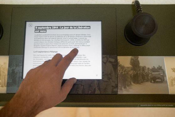Main qui touche l'écran de l'iPad pour lire les informations