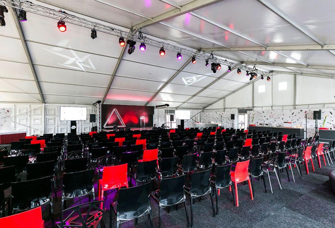 Alignement de chaises rouges et noires sous la tente de l'événement 85 ans de Ceratizit